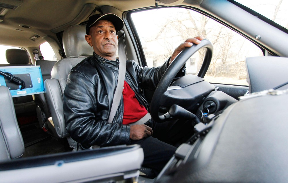Blue and White Taxi driver Zen Tesseena drove through downtown Minneapolis Monday while explaining new city ordinances for taxicab companies and drivers, including electronic credit card swipers, limited use of cell phones while driving and a dress code.