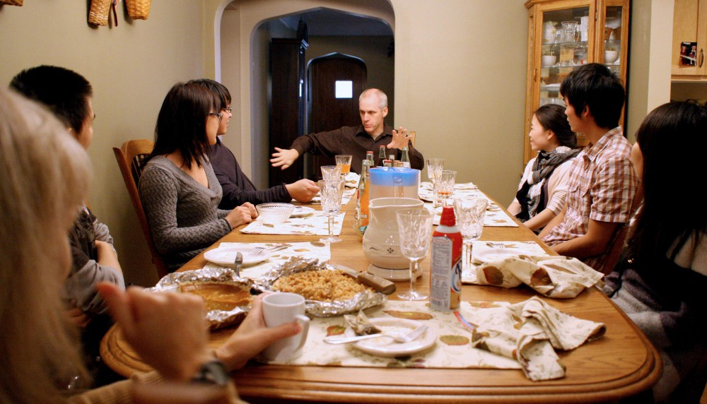 Host father Mark Hunt talks with Chinese exchange students at an early Thanksgiving dinner Sunday at the Hunts' home in Minneapolis. China Outreach Ministries organized an event for host families and students to talk about the meaning of Thanksgiving.