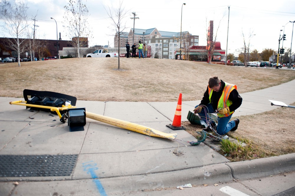 Electrician for the City of Minneapolis Joe Alford clears wires from the downed traffic light Wednesday at the intersection of Huron and University Avenues.