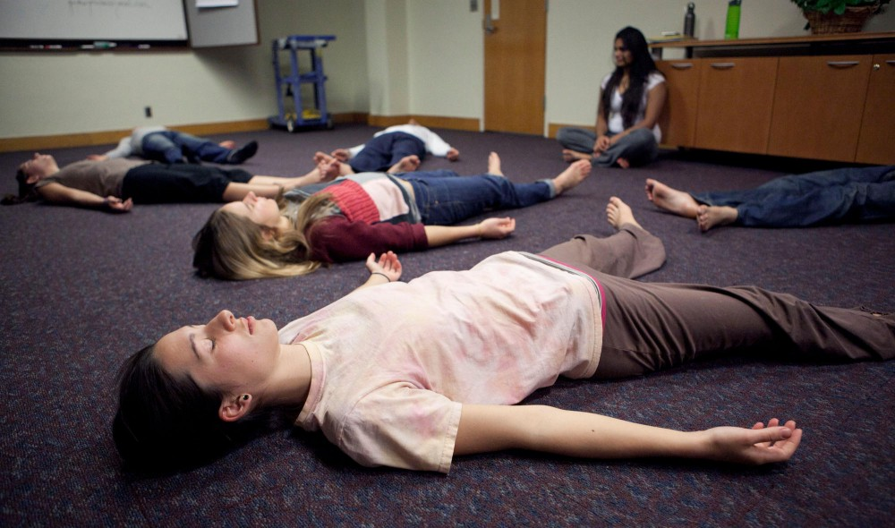 Anne Baggenstoss relaxes during meditation at the Yesplus workshop Wednesday night in the Saint Paul Student Center. The workshop is open to students and intended to teach methods to relieve stress and increase focus.