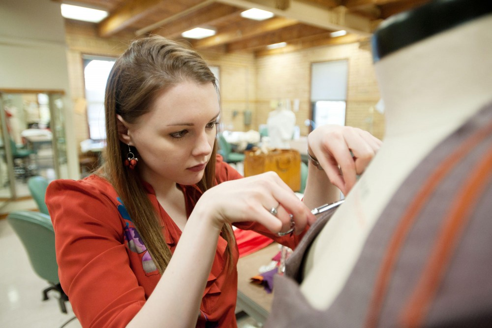 Senior apparel design student Lizzie Hillman tailors her garment Wednesday at McNeal Hall in St. Paul.