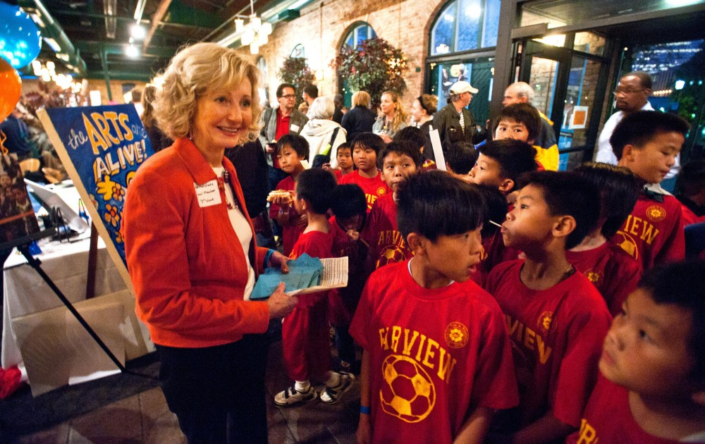 Third ward councilwoman Diane Hofstede greets the Farview soccer players at the door of the neighborhoodfest Oct.12 at the Nicollet Island Pavillon.