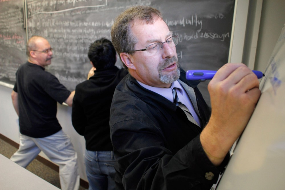Joe Klimek writes a response to a classmate on a marker board in the New Telecommunication Media class Thursday in Ford Hall. The class participates in a wide range of communication methods such as this pre-digital chat room format.