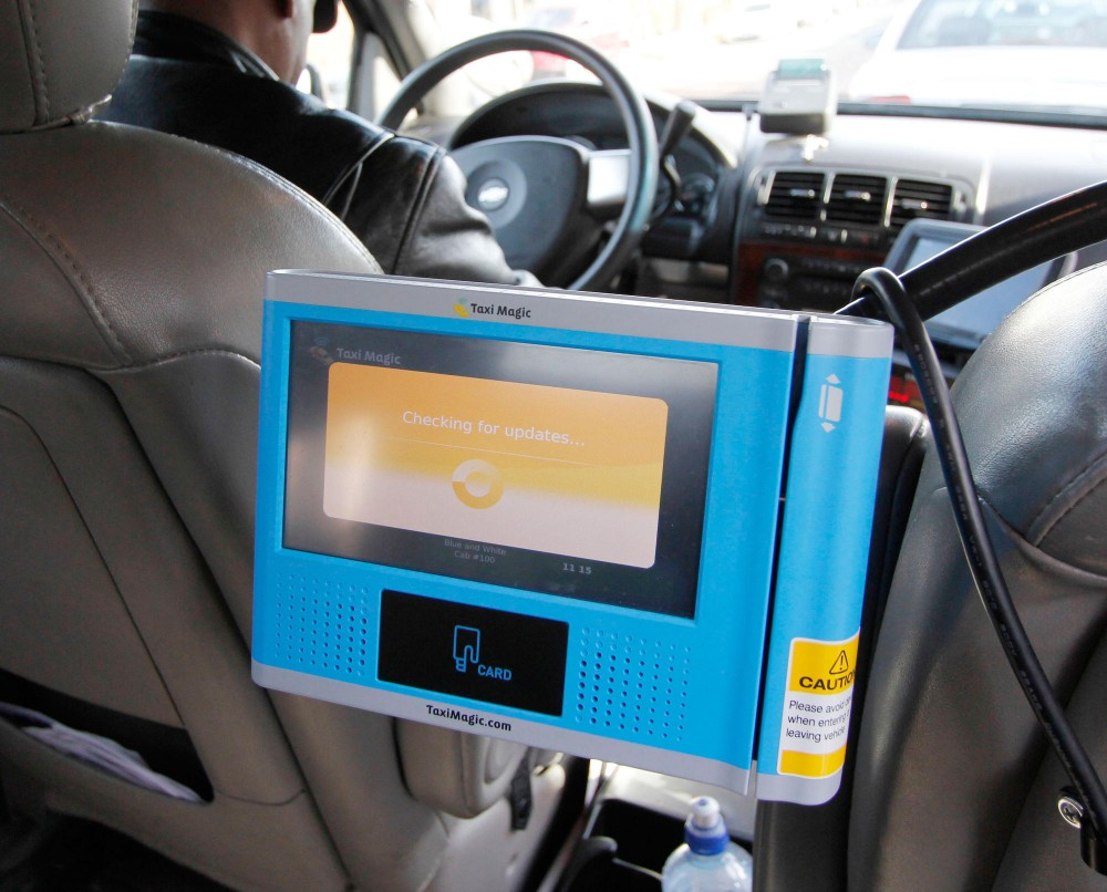 A new credit card swiper is built into the passenger area of this taxi. New Minneapolis city ordinances require electronic swipers, limited driver cell phone use and a dress code, among others.