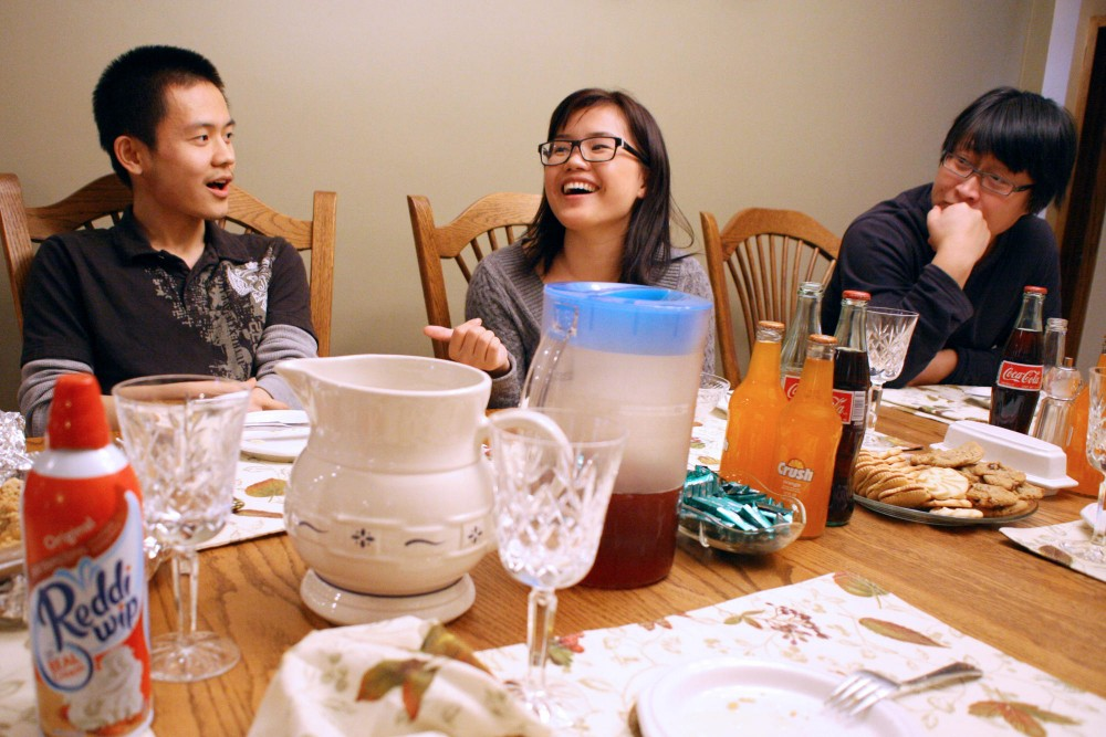 Chinese exchange students Bo Zhou, Su Weiping and Chile Litalk with their host mother Julie Hunt at an early Thanksgiving dinner Sunday at the Hunts home in Minneapolis.