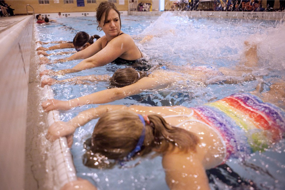 Swim instructor Dawn Pierson teaches girls in the Vikings Fitness Playbook weight-management program how to flutter kick Tuesday evening in the Cooke Hall pool.