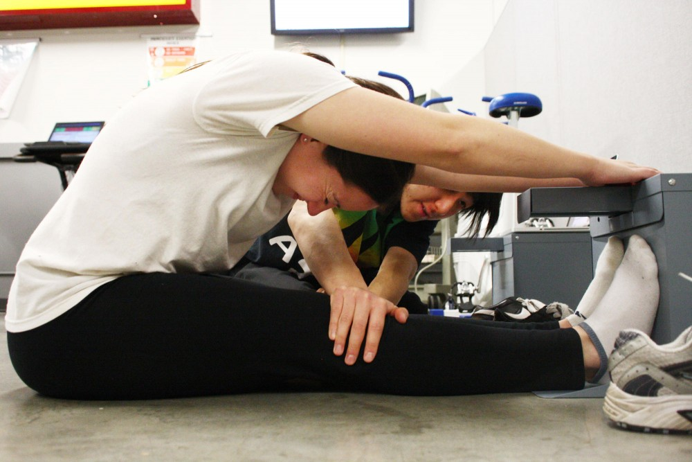 Keely Grimm and her lab partner Tu Nguyen measure their flexibility Friday at the Human Performance Teaching Laboratory.