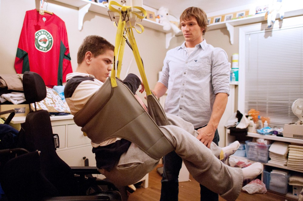 Anthropology junior Tim Clemens transfers Aaron Wager from his wheelchair to his bed with a ceiling lifting system Monday at Wager's home in MInneapolis. Clements works as a personal care assistant in the Wager's family.