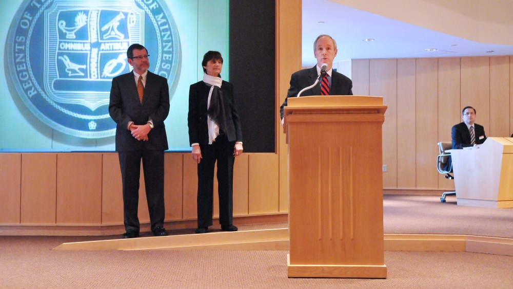 Tom Sullivan speaks Friday morning at the Board of Regents meeting at the McNamara Alumni Center, as President Kaler and Regent Board Chair Linda Cohen look on from behind.  Sullivan stepped down from his position as senior Vice President and Provost and was officially recognized by the Board during Friday's meeting, where the Regents discussed topics like finance and research.