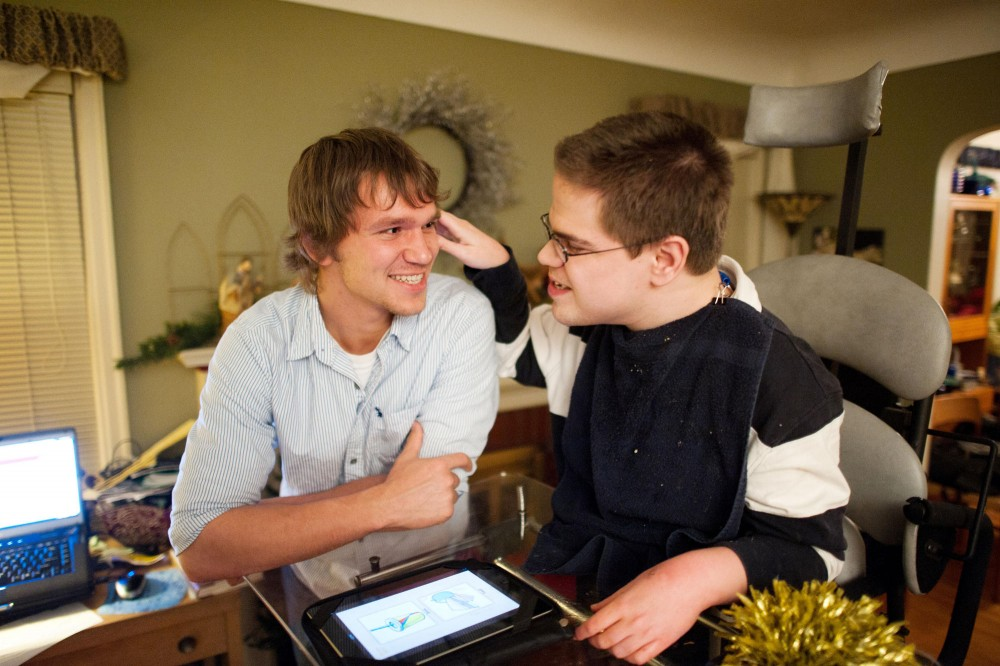 Anthropology junior Tim Clemens teaches Aaron Wager how to use a soundboard app on an iPad after dinner Monday at Wager's home in Minneapolis.