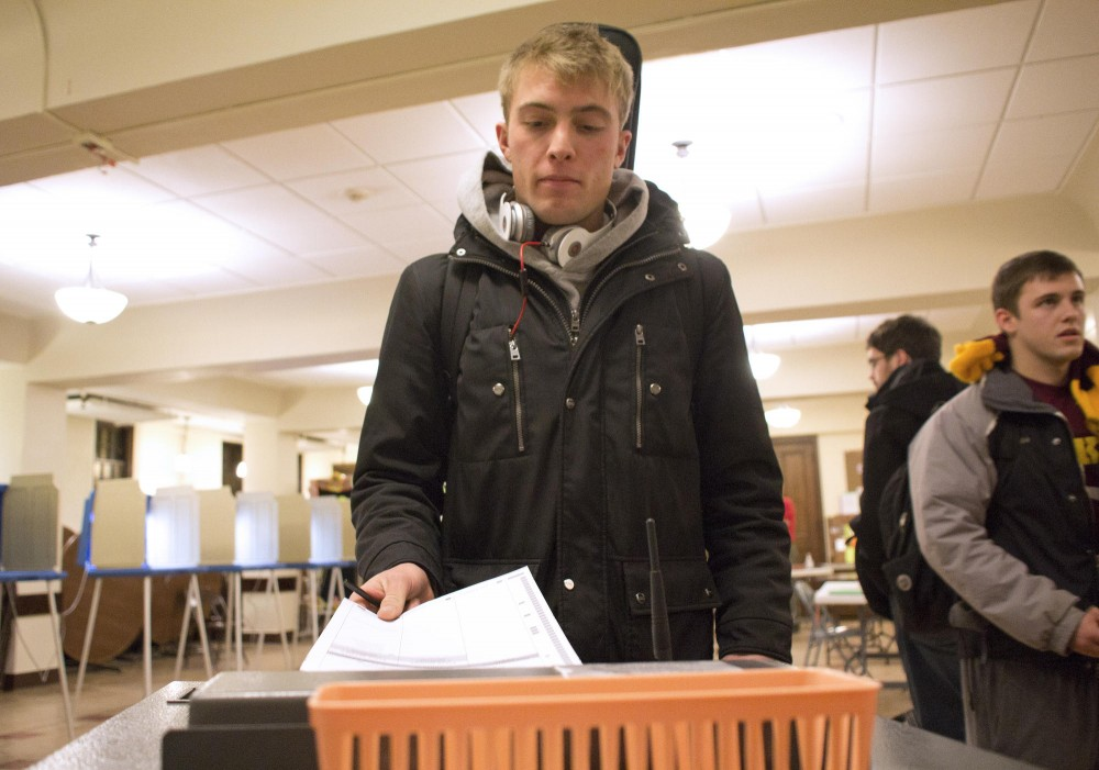 Sophomore and first-time voter Tommy Koehn submits his ballot for the DFL primary Tuesday at the Grace University Lutheran Church in Minneapolis.