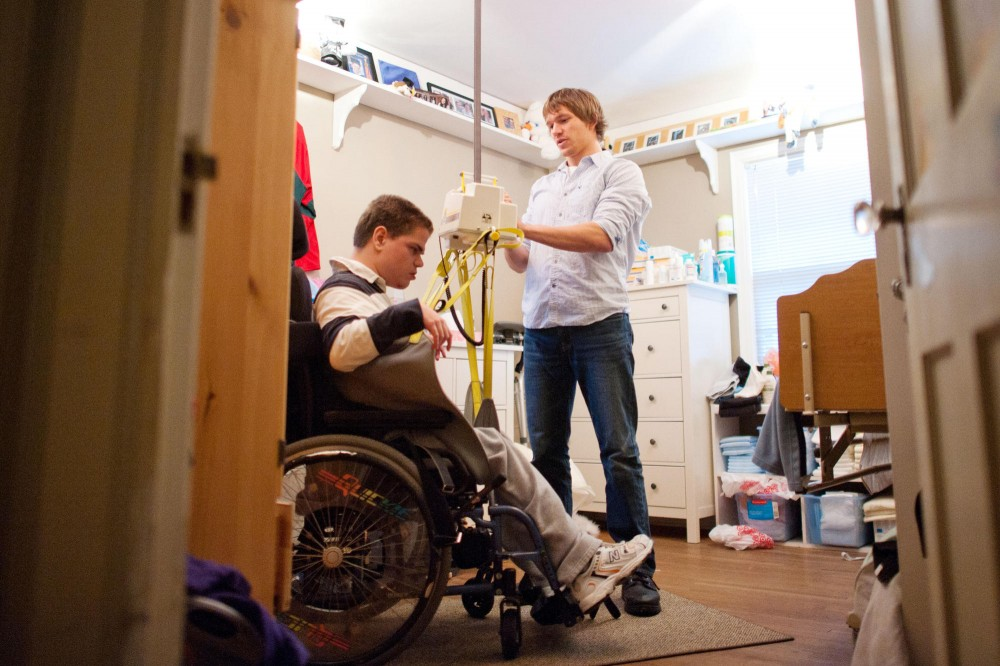 Anthropology junior Tim Clemens helps Aaron Wager to get on a lifting machine Monday at Wager's home in Minneapolis.