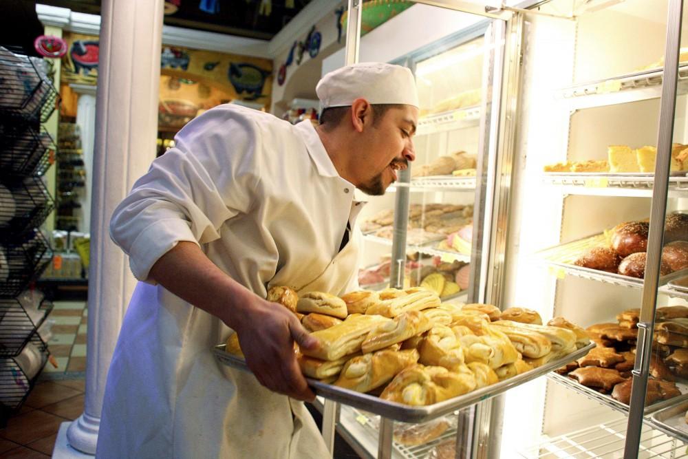 Alex Gonzalez loads a fresh pan of sweet bread Tuesday at La Alborada Market on East Lake St, Minneapolis.