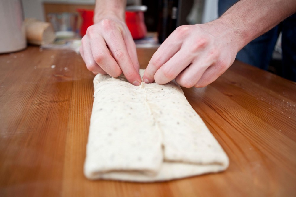 After the dough is folded, the seams should be pinched shut to keep the air from escaping. This helps the bread rise evenly while baking.