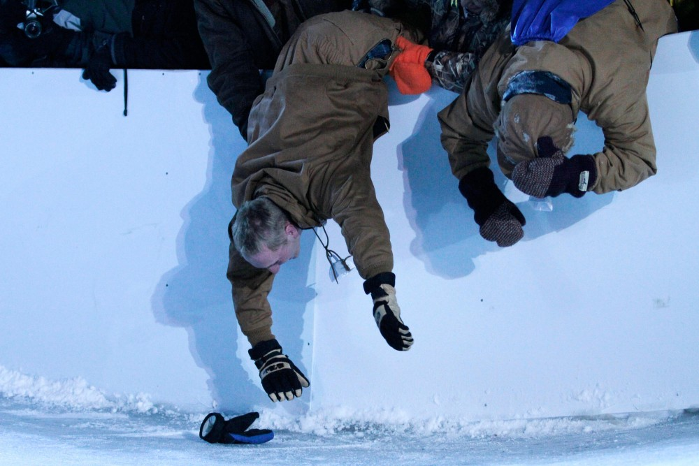Friends hold a fellow spectator as he reaches for a lost glove on the track Saturday night at the Red Bull Crashed Ice event in St. Paul.