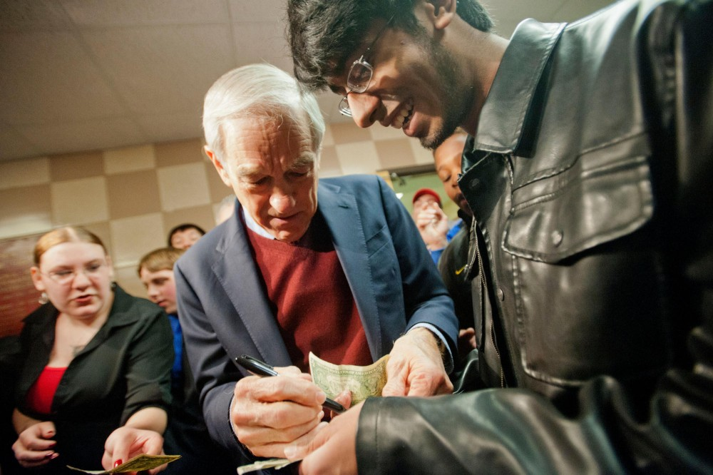 Republican presidential candidate Rep. Ron Paul, R-Texas, signs a dollar bill at a caucus site Tuesday night in Coon Rapids, Minn.