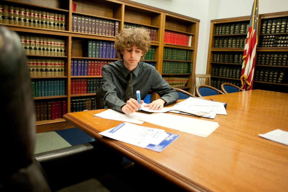 Political science major Alex Hellweg reviews a constituent's letter to Sen. John Harrington, DFL-St. Paul, on Tuesday at the State Office Building in St. Paul.  Hellweg and other legislative interns will no longer get paid for their time.