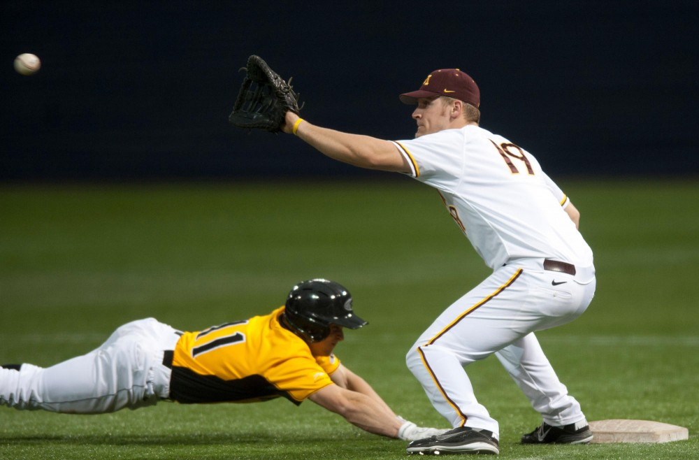 Gophers junior Ryan Abrahamson catches a pickoff throw from Austin Lubinsky as Milwaukee's Luke Meeteer slides back to the base Sunday at the Metrodome.