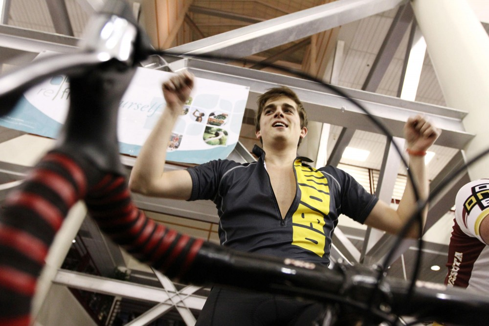 Parker Mullins, a junior in marketing, boogies on his bicycle to keep up his energy just after midnight on Friday at the Recreation Center. The University of Minnesota Cycling Team rode for 24 hours to raise money for the American Cancer Society.