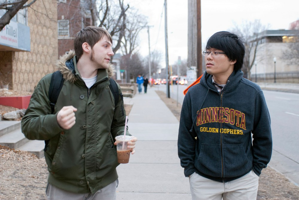 Sociology major and senior Andrew Ensign, left, and applied economics major Muqian Tian, junior, chat in English as they walk toward the bus stop Friday afternoon.  The students met through the University's TandemPlus program and get together to speak English and Chinese on a regular basis.