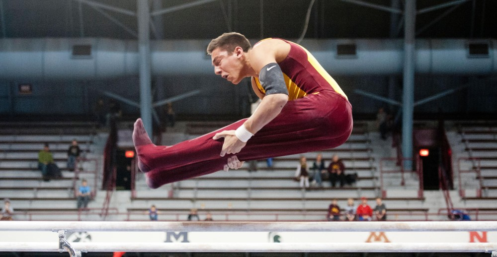 Gophers's freshman Steve Jaciuk in action on the parallel bars Saturday at Sports Pavilion. Jaciuk scored a career-high 14.4 in the parallel bars event.