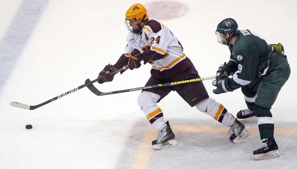 Gophers' forward Zach Budish fends off a Bemidji State defender during a game against the Beavers Feb 17 at Mariucci Arena. Budish scored two goals in the game to lift the Gophers to a 3-0 victory.