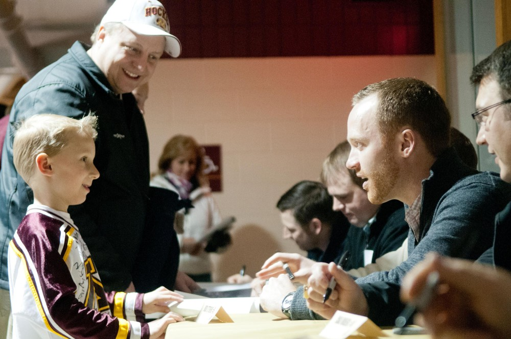 Judd Stevens, right, signs his autograph for young Gophers hockey fan Matthew Blodgett before Saturday nights game against Bemidji State.  Stevens was a member on the 2002 national championship team that defeated Maine 4-3 in the title game.