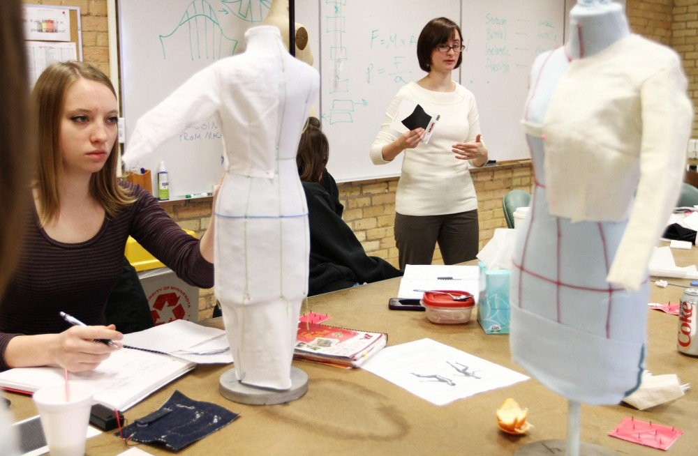 Associate professor of apparel design Dr. Lucy Dunne, left, gives instruction on impact protection, mobility, electronic textiles and thermal balance in a studio design class Tuesday in McNeal Hall. The class is working on a spacesuit design which they will present to NASA.