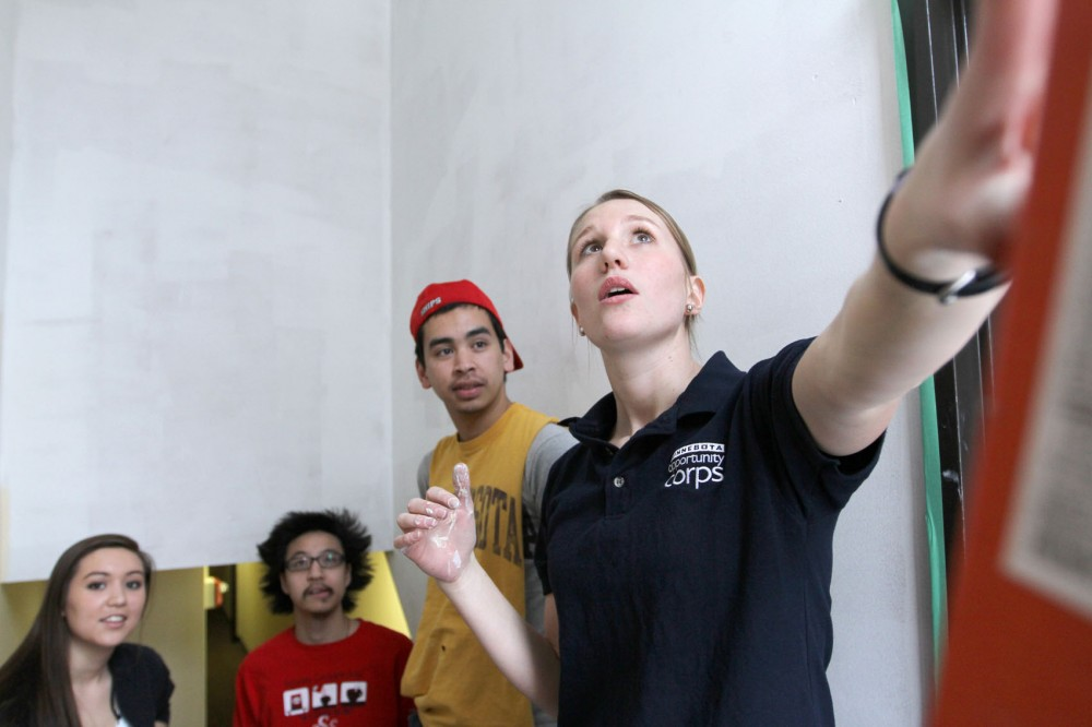 Laura Rescorla (right), a volunteer supervisor with Project for Pride in Living, gives University students an overview of the apartment they volunteered to paint Wednesday in South Minneapolis. From left to right, Simone Wai, Ken Chong and Robbie Anderson volunteered through Students Today Leaders Forever.