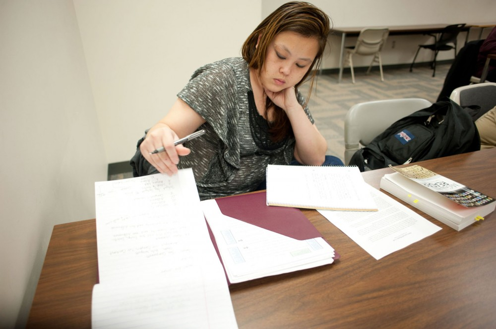 Marla Thao looks over notes during her Writing for Your Major class Feb. 16 at the Metropolitan State University in Minneapolis. Thao started college courses while serving a seven-year prison sentence for promotion of prostitution.