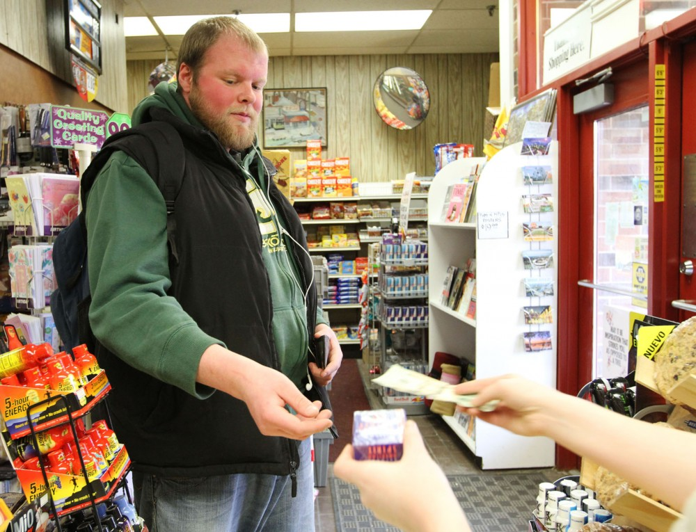 Senior and Chinese major Jake Imholte buys a pack of American Spirits on Thursday afternoon at House of Hanson. Imholte believes that the desire to smoke will trump the inconvenience of another potential tobacco tax increase.