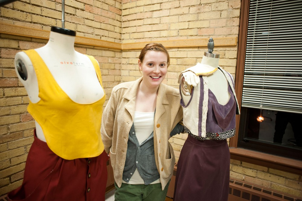 Design senior Kari Kachelmacher displays two of her pieces in the final stages of preparation on Tuesday in McNeal Hall.  The class's show,