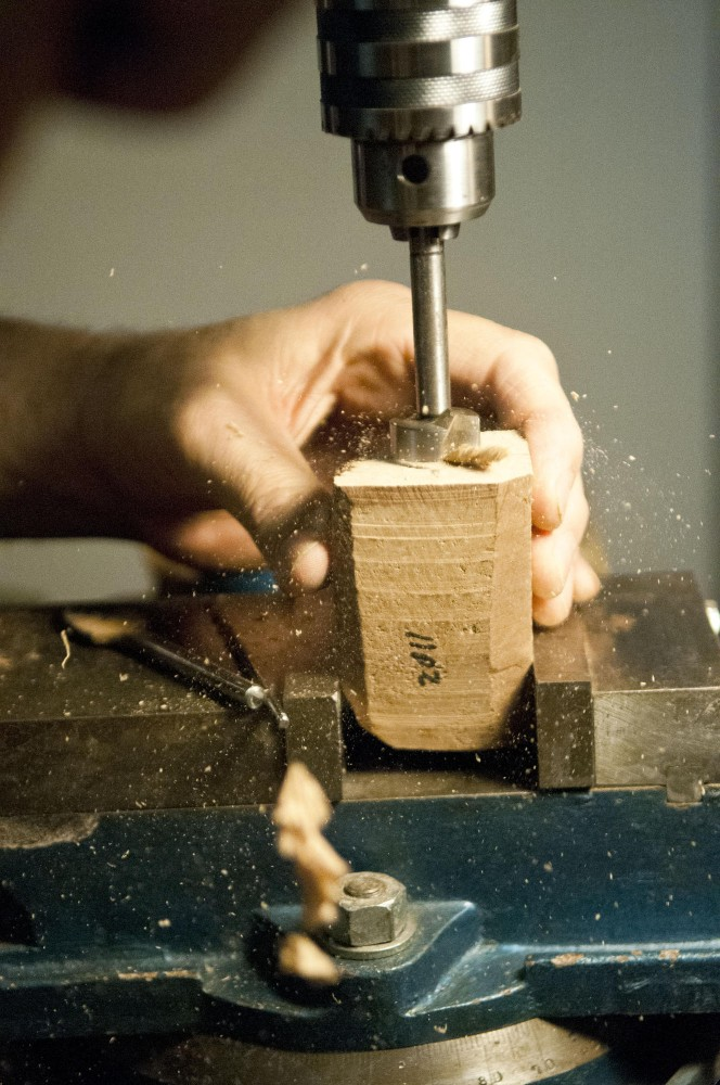 Rich Lewis works on a new pipe by drilling a hole into a block of briar.  Briar wood is often used in pipe making due to its natural resistance to fire.
