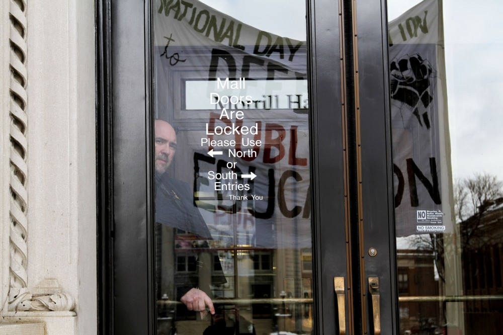A UMPD officer stood inside the doors of Morrill Hall on Thursday during the National Day of Action for Education Rights organized by Students for a Democratic Society on campus.