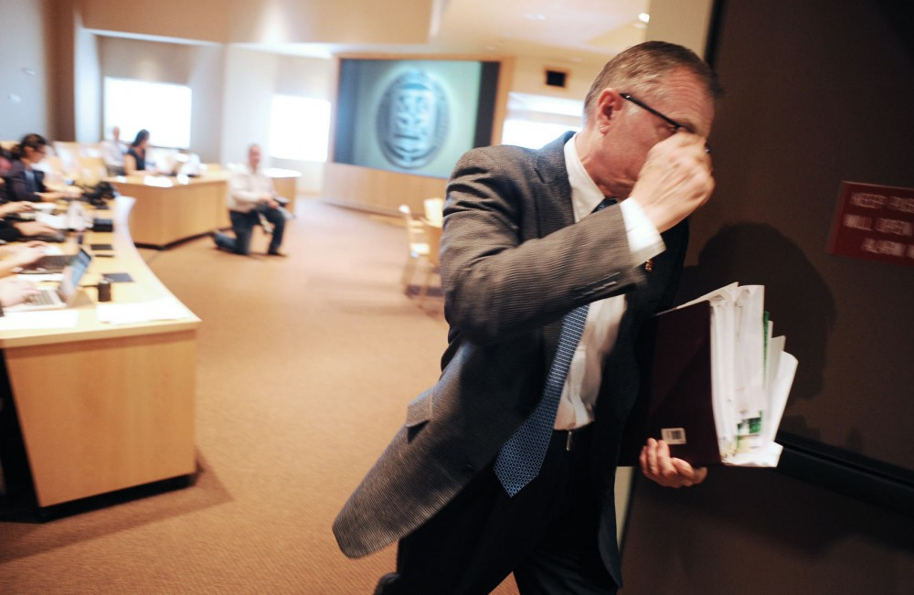 Regent Steve Sviggum walks out of a Board of Regents meeting after handing out a letter of resignation on Thursday at McNamara Alumni Center.