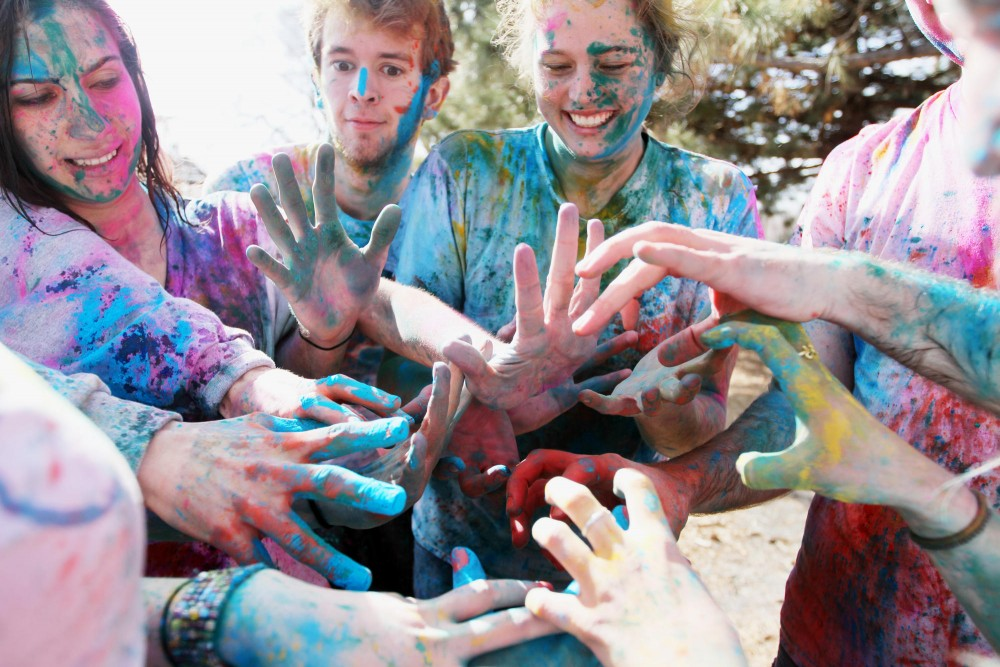 University students cluster their color covered hands in a circle while celebrating Holi, a festival of colors, on Tuesday at Van Cleve Park. Holi is a religious and cultural holiday that is meant to bring together all social classes, ages and genders to celebrate the colors of Spring.