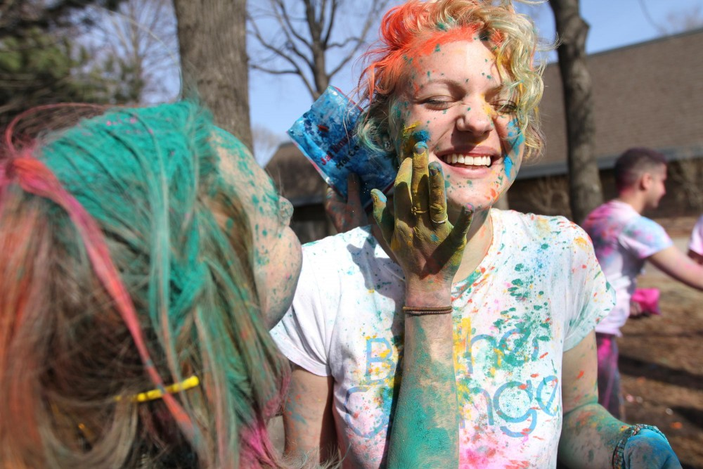 Theater Arts sophomore Nicole Kophmann receives a smothering of blue powder on Tuesday during a Holi function held at Van Cleve Park. Holi is primarily celebrated in India and surrounding countries.
