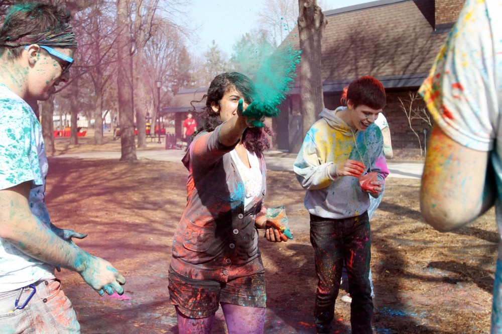 Sophomore Tina Ray throws a hand full of colored powder during a Holi event on Tuesday at Van Cleve Park. The event was organized by University students as a casual celebration of Spring.