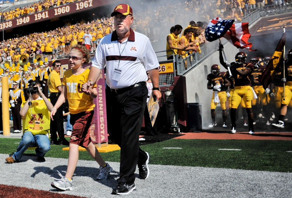 Minnesota head coach Jerry Kill and 10-year-old Mia Gerold walk onto the field before the start of the Gophers game against New Mexico State on Sept. 10, 2011 at TCF Bank Stadium.
