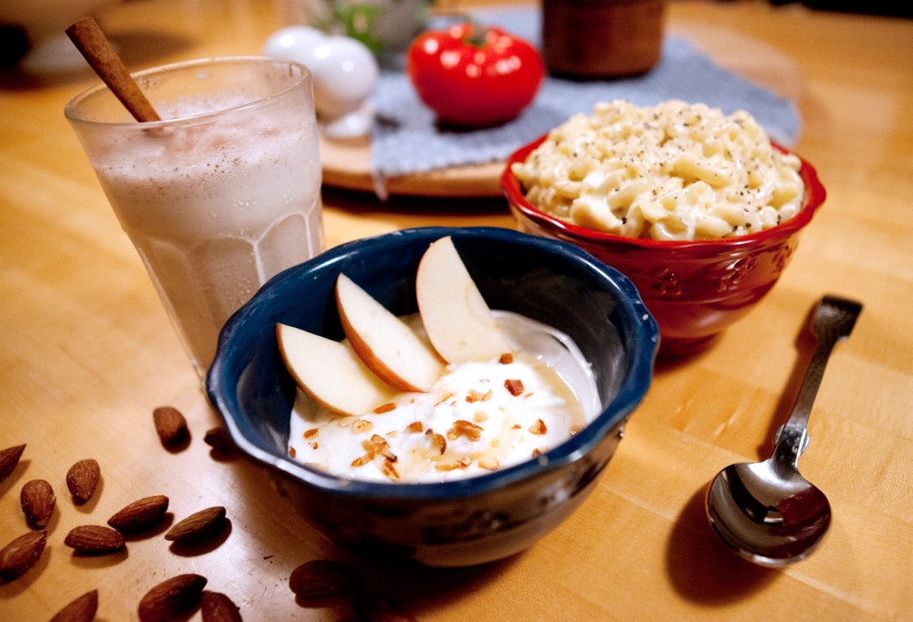 From back left to front: caramel milkshake, three-cheese mac n' cheese, and Greek yogurt with honey, almonds and apple. Eating dairy products as a source of protein reduces the need to buy expensive meat, which puts a dent on any college student