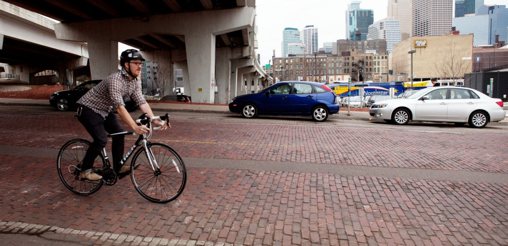 University of Minnesota alumnus Patrick Stephenson bikes to work on Wednesday at the Ford Center in Minneapolis. Patrick co-founded 30 Days of Biking, a pledge made by participants to bike everyday.