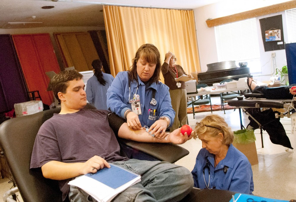 Mechanical engineering sophomore Travis Evans, left, donates blood with the help of Red Cross phlebotomists Stacy Hauer, center, and Sandy Gapinski, right, on Tuesday.  Evans attended the Alpha Epsilon Pi blood drive at Hillel at the suggestion of a classmate.
