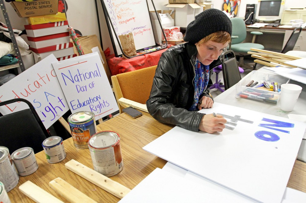 Freshman English major Rachel Hauser designs protest signs for the National Day of Action for Education Rights, a march and rally happening Thursday at Morrill Hall.