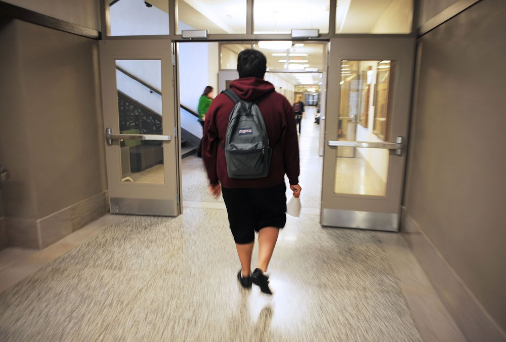 Apolinar walks to his Chicano studies class Tuesday in Folwell Hall. Though Apolinar was born in California and grew up in St. Paul, Minn., his parents live in the country illegally.