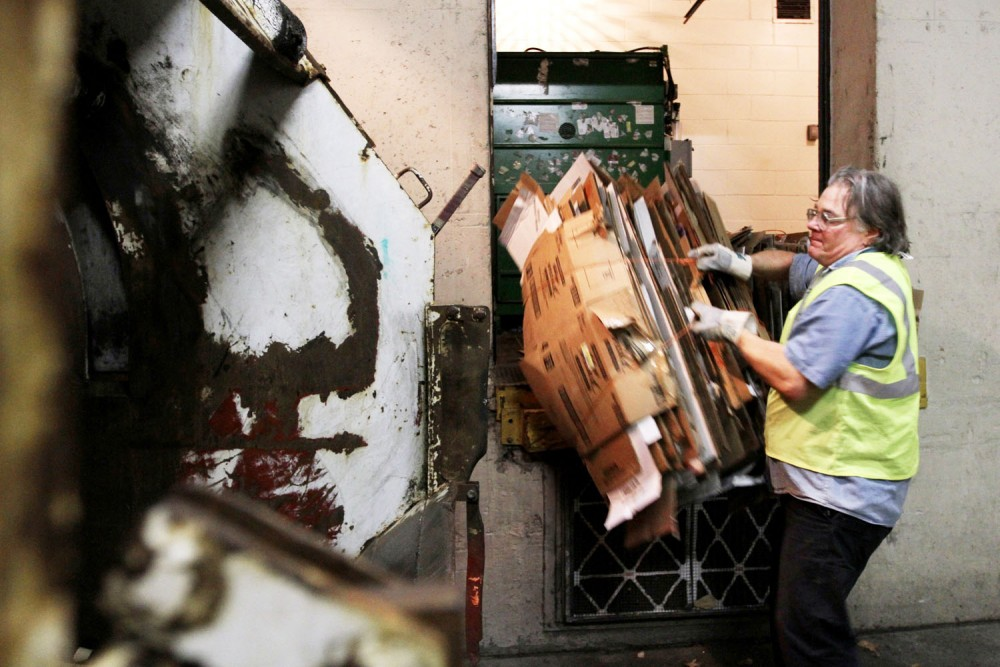 A facilities worker removes cardboard from the loading dock at 5:30 a.m. on March 21 at Centennial Hall.