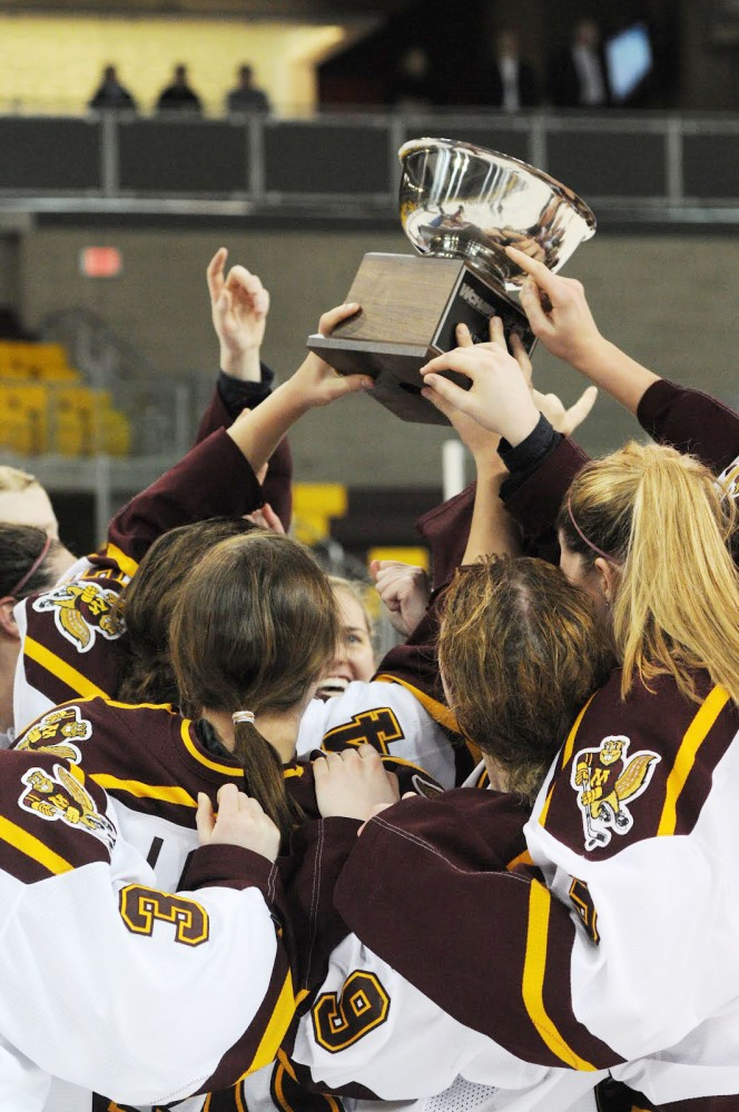 A group of Gophers celebrate with the championship trophy. The Gophers beat Minnesota-Duluth 2-0 to claim their first title tournament title in seven years.