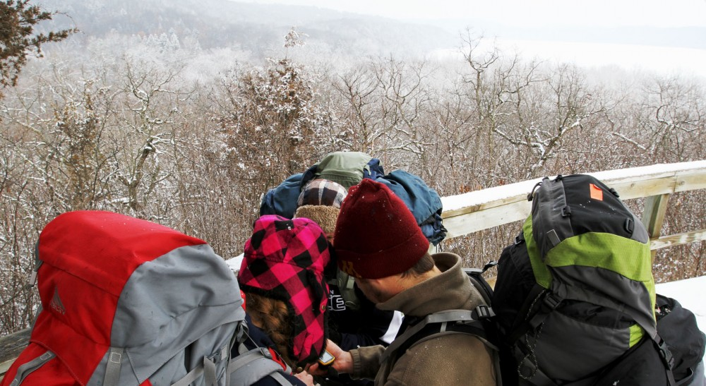 Recreation, park and leisure studies majors huddle around a GPS device while geocaching Friday at Afton State Park. Many students in the major will go into the service industry, which is expected to grow 17 percent from 2010-20.