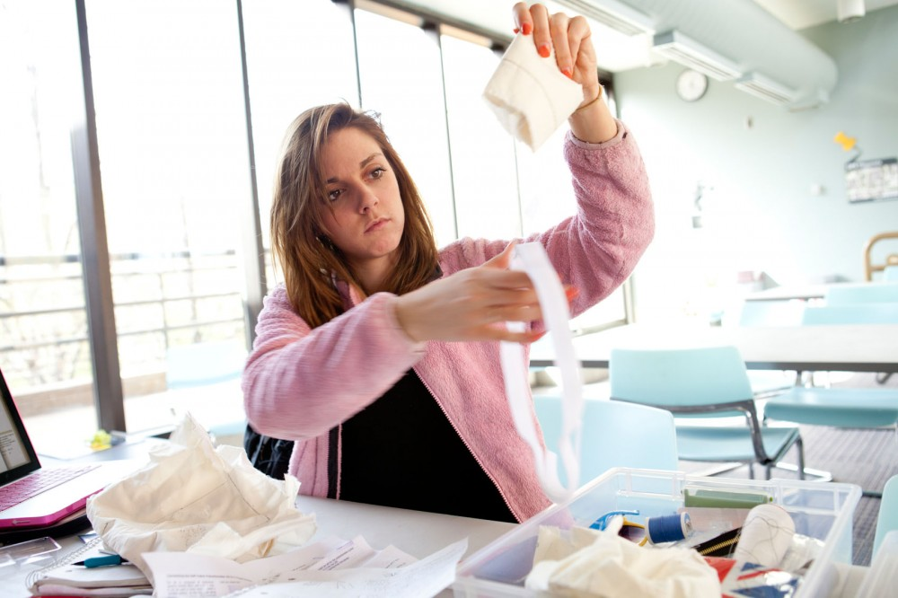 Apparel design junior Kaila Bibeau looks through different types of fabric that can be used to insult space suits for a group project in her apparel design class.