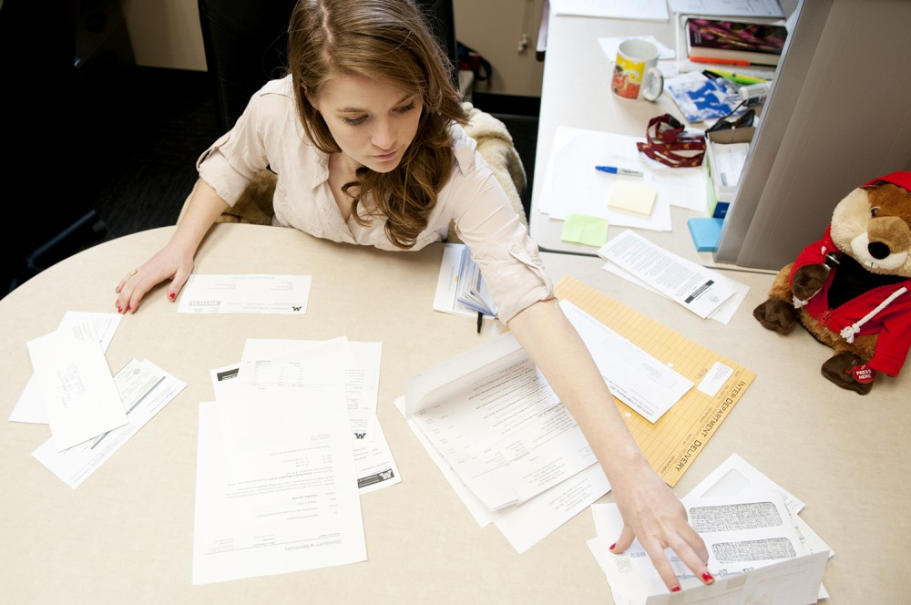 Undergraduate student body president Lizzy Shay, a finance junior, writes out checks Monday afternoon in her Coffman Memorial Union office. Shay has been president for the 2011-12 academic year and will step down June 30.