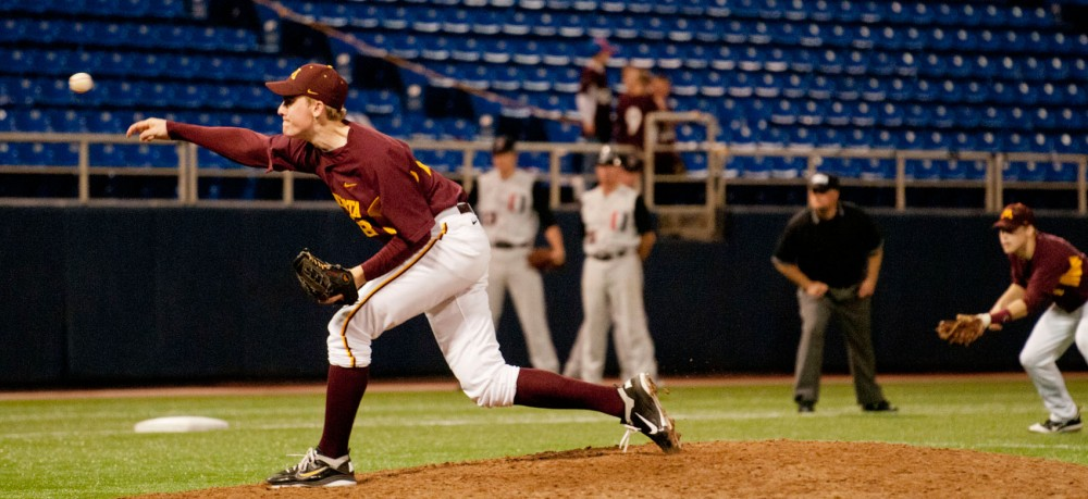 Gophers pitcher Ben Meyer pitches as members of both teams look on in anticipation Tuesday night at the Metrodome.